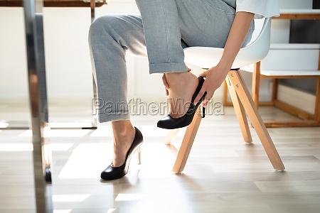 geschaeftsfrau leidet unter beinschmerzen wegen schuhen