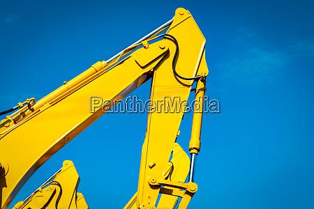 gelber bagger mit hydraulischem kolbenarm gegen