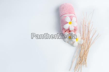 gerolltes rosa spa handtuch und frangipani