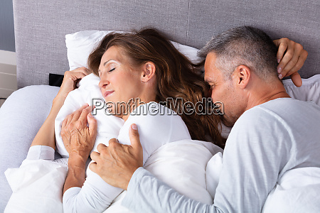 couple sleeping on bed with blanket