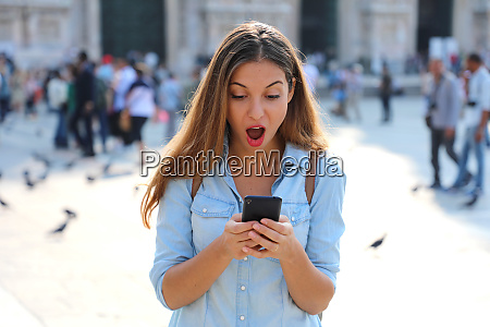 surprised young woman using smart phone