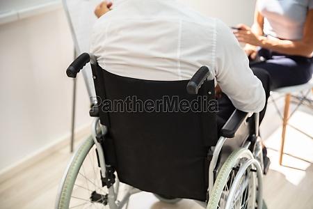 behinderter geschaeftsmann in der versammlung