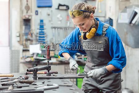 frau mechaniker in metallerner werkstatt