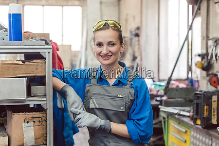 arbeiterin in metallwerkstatt schaut in kamera