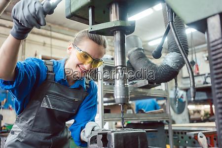 arbeiterin in metallwerkstatt mit sockelbohrer