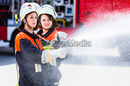 female fire fighters spouting water to