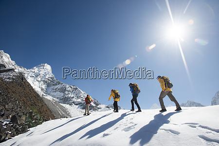 a team of four climbers make