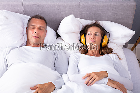 woman covering her ears with headphones