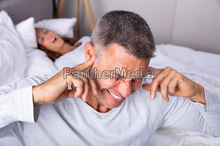 an angry man with snoring wife