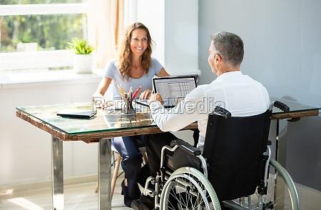 behinderter geschaeftsmann arbeitet auf laptop