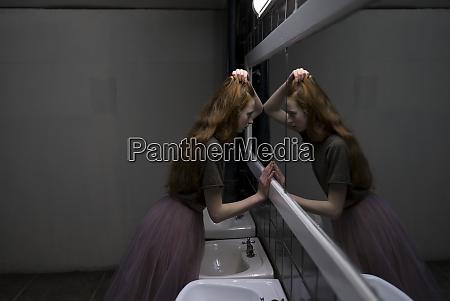 junge frau lehnt sich auf badezimmerspiegel