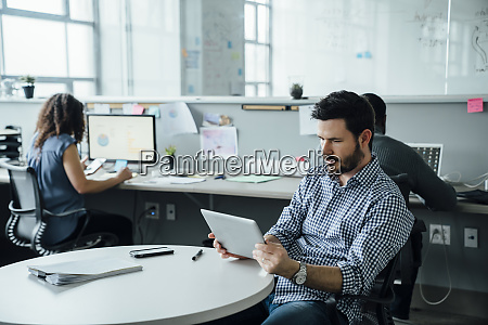 mann mit digitalem tablet im buero