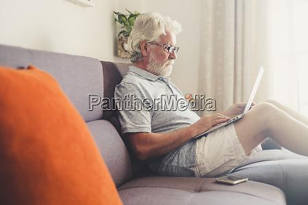 senior mann mit laptop auf sofa