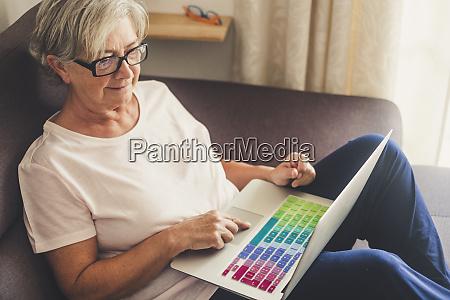 seniorin mit laptop auf sofa