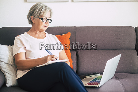 senior frau haelt stift mit laptop