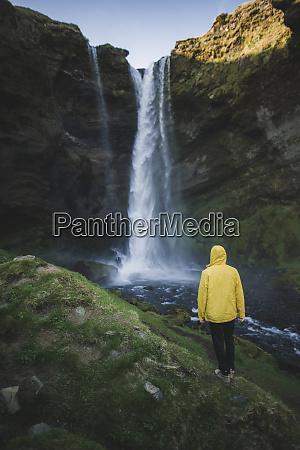 mann im gelben regenmantel von kvernufoss