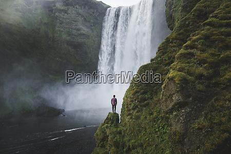 mann am skogafoss wasserfall in island