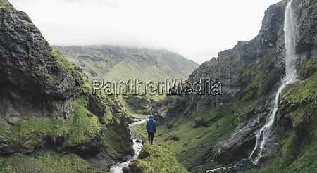 mann wandert am wasserfall in island