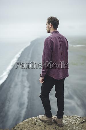 mann traegt lila hemd ueber strand