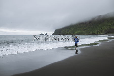 mann joggt am strand in vik