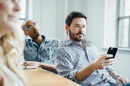 mann haelt smartphone waehrend der sitzung