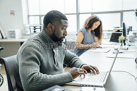 mann mit laptop im buero