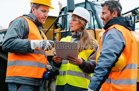 three workers in a quarry discussing