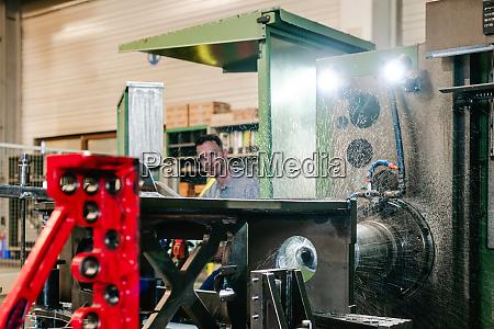 arbeiter der eine industrielle fraesmaschine betreibt