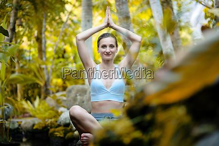 frau macht yoga im tropischen dschungel