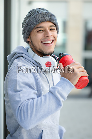 smiling young latin man drinking sports