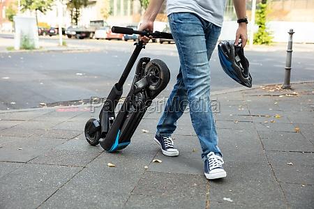 mann der e scooter zur arbeit