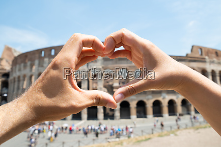 couple making heart shape in front