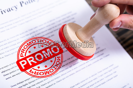 businessman putting promotion stamp on document