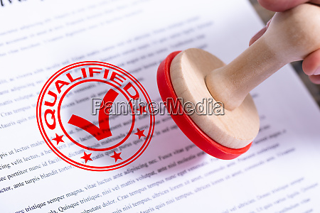 businessman putting qualified stamp on document