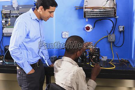 schueler untersuchen kondensatorspule auf kaelteanlage im