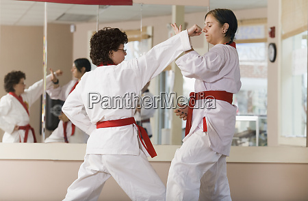 young woman practicing karate with a