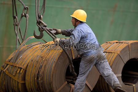 maennlicher bauarbeiter der kabel an metallspulen
