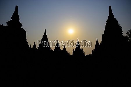 silhouetted buddhist temple at sunset bagan