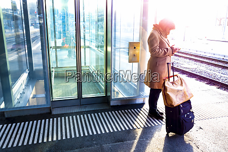 a woman stands with her suitcase