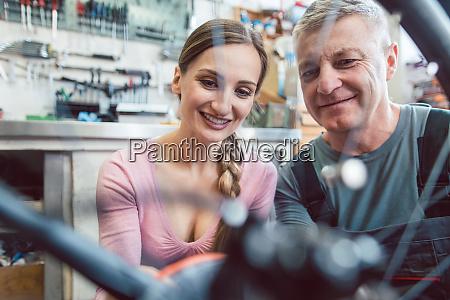 bike mechanic and customer looking at