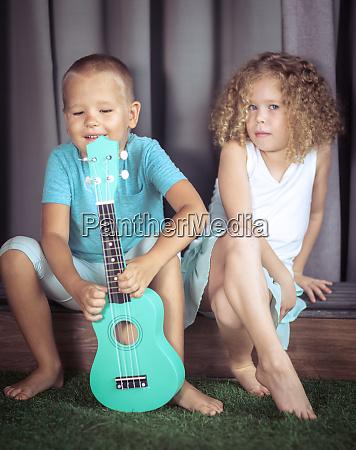 portraet eines niedlichen kindes mit ukulele