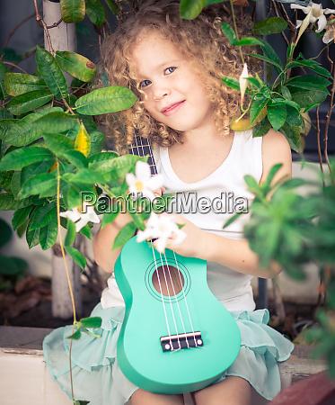 portraet eines niedlichen maedchens mit ukulele