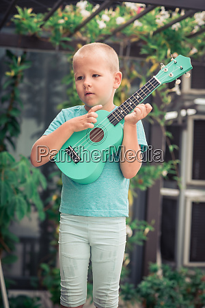 portraet eines niedlichen jungen mit ukulele