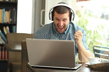 aufgeregter mann mit kopfhoerern ueberprueft laptop