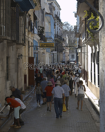 havana cuba people walk along empedrado