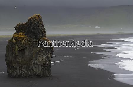 iceland vik basalt column rises from