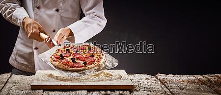 chef macht eine hausgemachte pfefferoni pizza