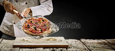 koch entfernt eine salami pizza aus