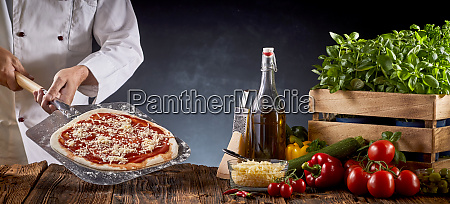 chef making a traditional margherita pizza