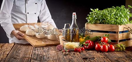chef in einer pizzeria bereitet italienische